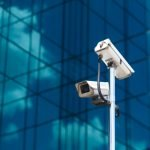 pole-with-two-white-video-surveillance-cameras-big-office-glass-building